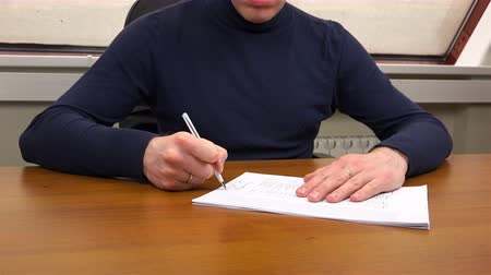 faktura : A man at the office signs a contract.