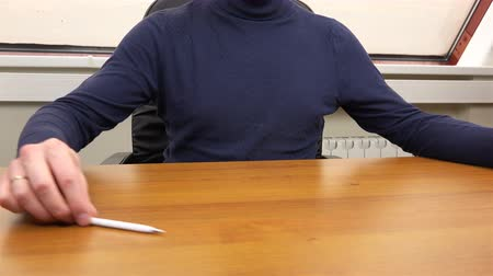 dikkatli inceleme : Office worker sits at a table with a pen and papers.