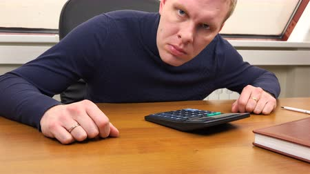 calculadora : An office worker peers into the camera lens and faces a finger.
