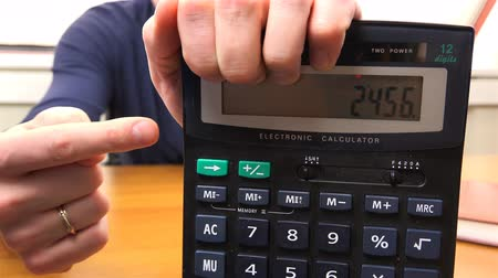 összeg : Mens hand points to the amount in the calculator. Stock mozgókép