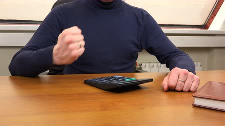 účty : A man counts on a calculator and rubs his palms.