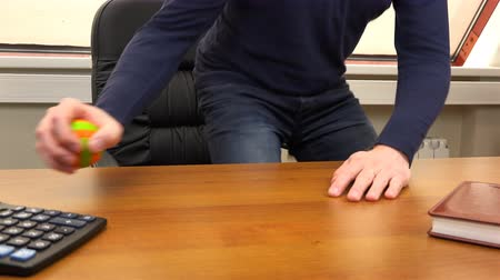 satmak : A man spins a small ball on an office desk.