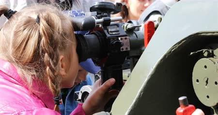 defensiva : Russia, St. Petersburg, September 02, 2018 a girl with pigtails looks into the gun sight at the exhibition of military equipment. Stock Footage