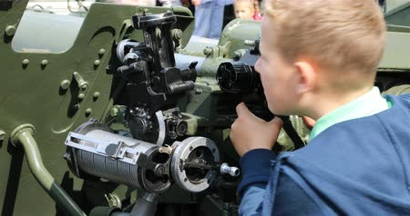 defensiva : Russia, St. Petersburg, September 02, 2018 a boy is studying with interest the device of an anti-aircraft gun.