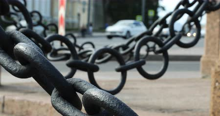 architectural protection : pedestrians can be seen through large black chains.