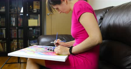canvas : a woman holds a canvas on her lap and draws,