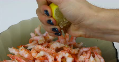 király : female hand squeezes juice from lemon into king prawns. Stock mozgókép