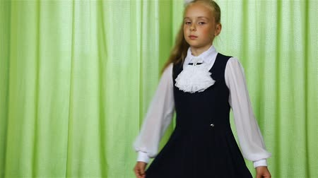 solene : girl spinning in school uniform on a green background.