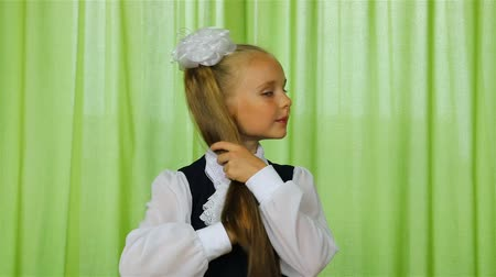 ünnepélyes : a first grader in school uniform strokes the tail of light blond hair.