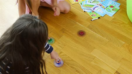 fascination : girls spin multi-colored spinners on the floor.