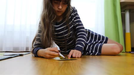 kleurplaten : a girl in a striped dress draws on the floor.