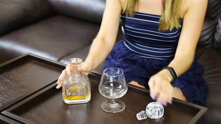 alkoholismus : a girl pours alcohol from a carafe into a glass.