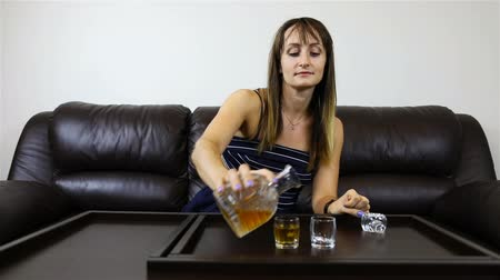 hangover : a woman fills glasses with alcohol and offers her companion to drink.