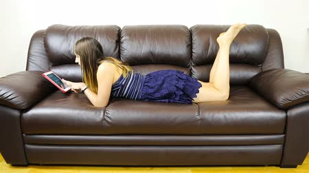брюнет : brunette lying on the couch working with a tablet.
