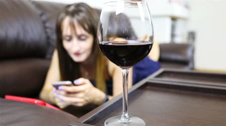confortável : a girl works on a smartphone with a glass of red wine. Blurred background.