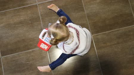 младенчество : The child is playing with the children s phone on the ground. Top view.