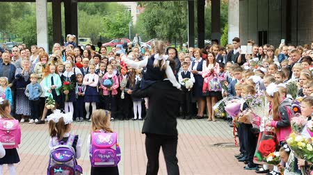 first class : Russia, St. Petersburg, September 1, 2018 High school student is carrying the first-grader with the bell in his arms