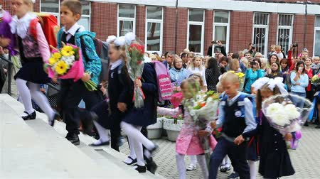 first class : Russia, St. Petersburg, September 1, 2018 First grade pupils are entering the school in pairs holding flowers