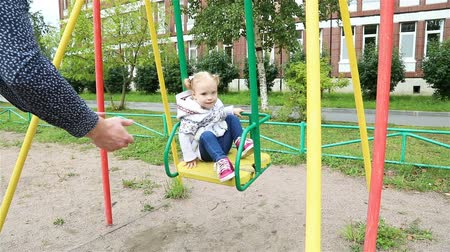 детская площадка : The father offers his hand to the daughter and helps her to get off the swings.