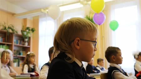 opinion : Russia, St. Petersburg, September 1, 2018 The first-grader in glasses is on the lesson at his desk in the school