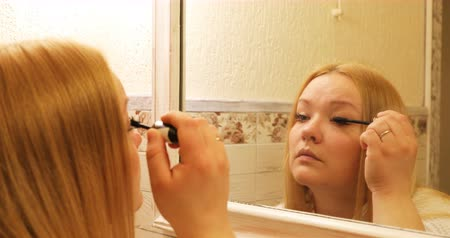 стегать : The woman is carefully putting black mascara on her lashes. Стоковые видеозаписи