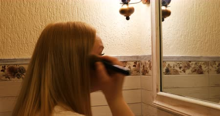 стегать : The girl is putting the powder on her face in the bathroom.