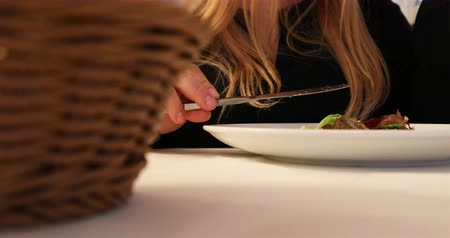 císař : The girl at the white table is eating the salad using the fork and the knife.