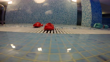 аксессуар : There are red rubber slippers near the swimming pool. Стоковые видеозаписи