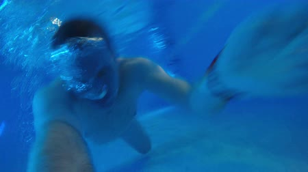 plavec : Young man is swimming under the water in the pool.