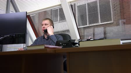 forródrót : the man listened to comments on the work on the phone and continued to work. Stock mozgókép