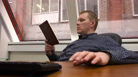 irodalom : tapping his fingers on the table, the guy is studying the work plan. Stock mozgókép