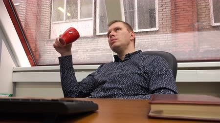 умный : resting at a desk, an employee is drinking tea.