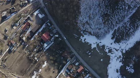Two cars leave on a narrow village road. Aerial survey.