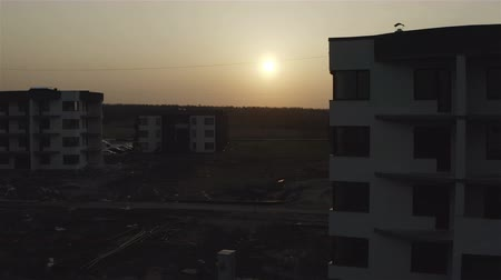 soaring over apartment buildings at sunset day. Wideo