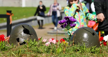 szegfű : Broken helmets of soldiers from military operations strewn with flowers.