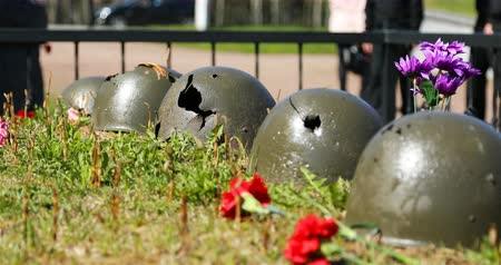 szegfű : punched soldiers helmets on the mass grave are laid out as a memory of soldiers. Stock mozgókép