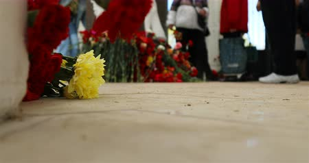 headstone : On Victory Day, people lay flowers at the grave of soldiers who died during the war.