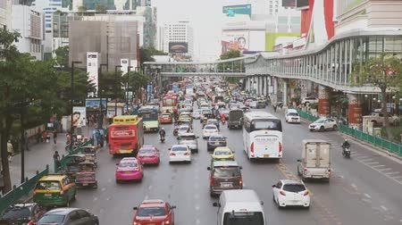 мощеный : Bangkok, Thailand. November 23, 2018 : Traffic jam at downtown in Bangkok city shows many buses and cars slowly running on the road with shopping malls along the roadside.