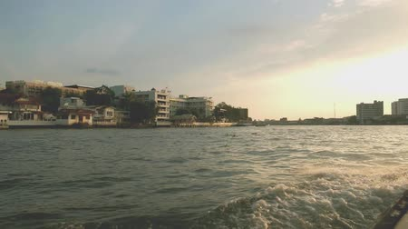 waterways : Boating on the express boat at Chao Phraya river in the evening, viewing local settlement along the riverside at sunset. Bangkok, Thailand.
