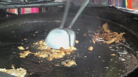 omlet : Vendor cooking Thai street food, Hoy Tod or fried mussels with egg with much oil in flat iron pan. Greasy food contains high cholesterol causing obesity and cardiac disease.