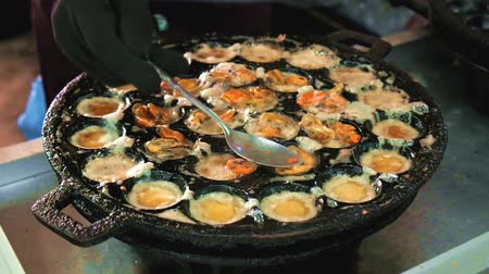 exotic dishes : Street food in Thailand. Fried egg with mussels cooked in Kanom Krok iron pan. Seller cooking Thai seafood for sale in the Bang Namphueng Floating Market, Bang Krachao.