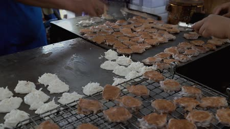 friandise : Vendors cooking authentic Thai dessert called Kanom Babin on a hot griddle. Traditional sweet coconut pancake frying for sale in a local market in Bang Kachao, street food in Thailand.