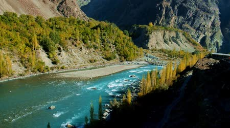 gilgit baltistan : Turquoise blue water of Ghizer river flowing through forest in Gahkuch surrounded by Hindu Kush mountain range. Autumn scenery in Gilgit Baltistan, Pakistan. Stock Footage