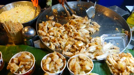 kalmar : Asian street food chef cooking stir-fried squid eggs for sale in a local market in Bangkok, Thailand.
