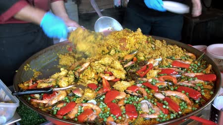 bezelye : Chef cooking traditional Spanish paella with prawn, chicken, mussels and red pepper a in a big pan and serving for sale in local street food market.
