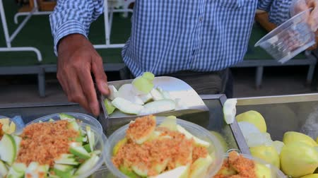 pronto a comer : Thai vendor chopping fresh guava fruit into bowl and sprinkle with spicy and sweet salt dips on top. Ready-to-eat tropical fruit for sale in local street food market in Bangkok, Thailand.