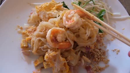 exotic dishes : Foreign traveler try Asian food dish Pad Thai noodle with shrimps for first time, use chopsticks pinching its ingredients in the plate. Authentic local street food in Thailand.