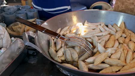 fish ball : Vendor frying Thai style fishballs for sale in local street food market in Bangkok, Thailand.