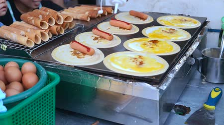 nekvalitní potraviny : Bangkok,Thailand. November 18,2019 : Business owner vendor making Thai style pancake roll (Kanom Tokyo) stuffed with sausage and egg on the pan for sale. Street food in local market. Dostupné videozáznamy