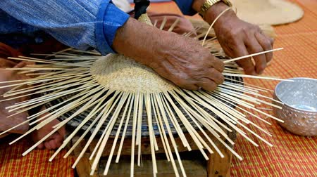 vime : Hands of old artisan craftsman elderly working weaving rattan and bamboo to make ancient handmade handcraft wicker traditional Thai wooden hat in Thailand